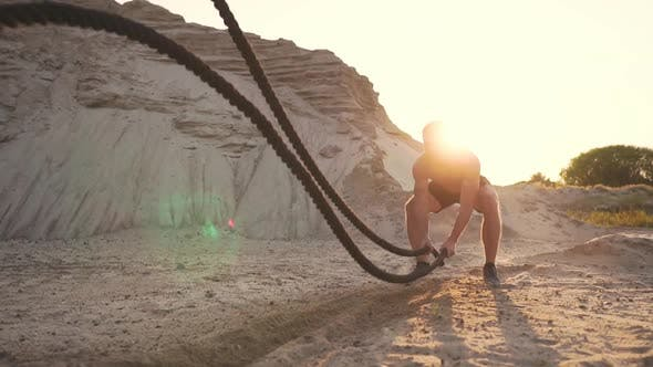 Cover Image for Male Athlete push-UPS on the Beach and Hits the Ground with a Rope, Circular Training in the Sun