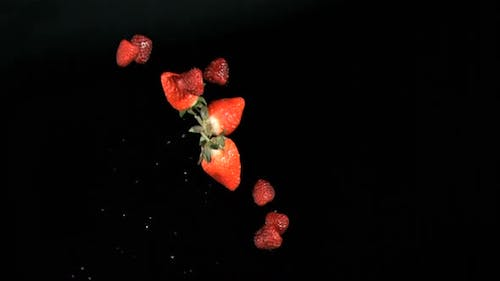 Red fruits being throw in super slow motion