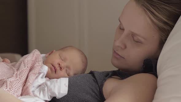 Mother and Newborn Daughter Sleeping Together in Daytime