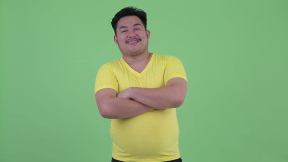Thumbnail for Happy Young Overweight Asian Man Smiling with Arms Crossed