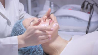 Cosmetologist Performs the Procedure of Cleansing and Moisturizing the Skin