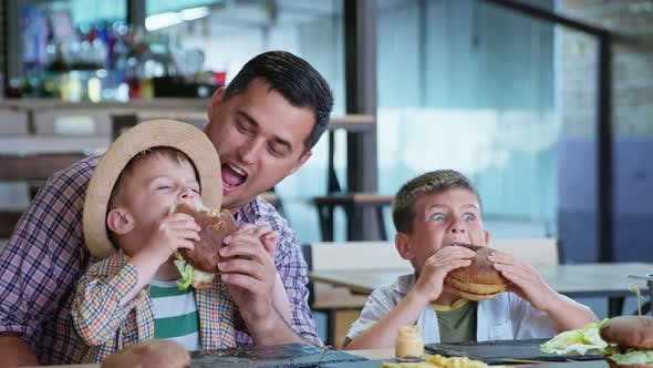 Cover Image for Children Eat, Happy Cheerful Male Parent Together with His Hungry Sons Enjoys Eating Tasty Burgers d