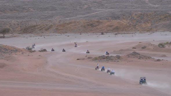 Thumbnail for Group on Quad Bike Rides Through the Desert in Egypt on Backdrop of Mountains