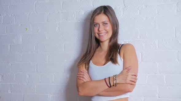 Thumbnail for Young Attractive Female Smiling And Looking At Camera While Leaning Against A White Brick Wall