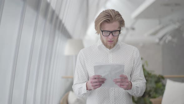 Cover Image for Portrait Successful Blond Man in Glasses Standing in a Light Comfortable Office Reading Papers