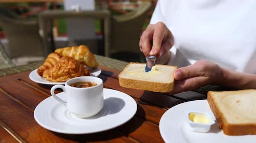 Hand Spreading Butter On Toast Having Breakfast With Coffee And Croissants.