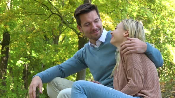 Thumbnail for A Young Attractive Couple Sits in a Park on a Sunny Day and Waves at the Camera with a Smile