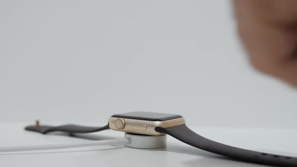 Smart Watch Charging on Wireless Charging Stand Pad on White Table