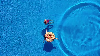 Aerial View of Man Dives Into the the Pool While Girl Is Lying on a Donut Pool Float