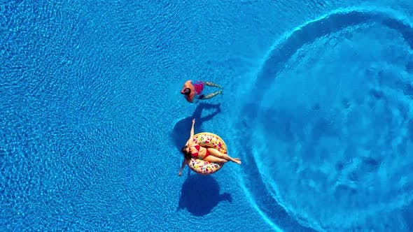 Thumbnail for Aerial View of Man Dives Into the the Pool While Girl Is Lying on a Donut Pool Float