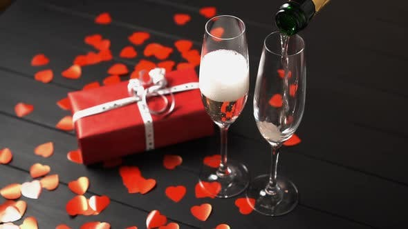 Thumbnail for Champagne Is Filled Into a Glass on a Black Table Near a Gift Box.