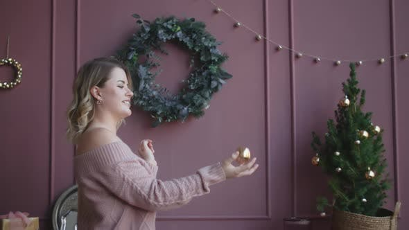 Thumbnail for Attractive Woman in Sweater Throws Up a Christmas Ball in Slow Motion, Decorating the Christmas Tree