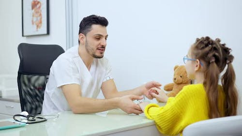Middle Shot of Joyful Male Pediatrician Holding Hands of Patient Talking and Smiling