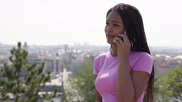 Thumbnail for A Young Black Woman Talks on a Smartphone - a Cityscape in the Blurry Background