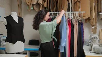 Tailor's workshop. Hanging clothes on a hanger. Clothes designer looking on a hanger