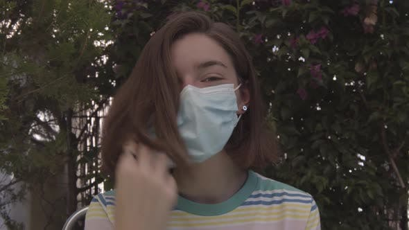 Thumbnail for Young teenage girl taking off her face mask  in the garden