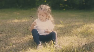 Little Girl Looks at Metal Spoon Holding Yogurt Container