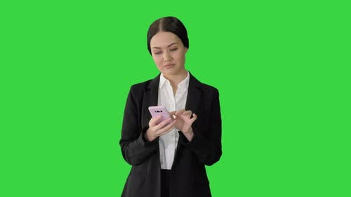 Casual Female in a Suit Texting on Her Phone on a Green Screen Chroma Key