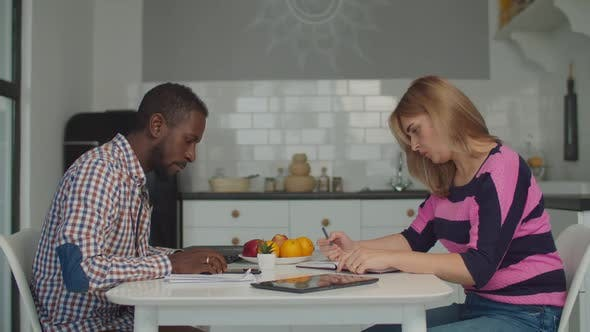 Thumbnail for Diverse Couple Managing Family Budget in Kitchen