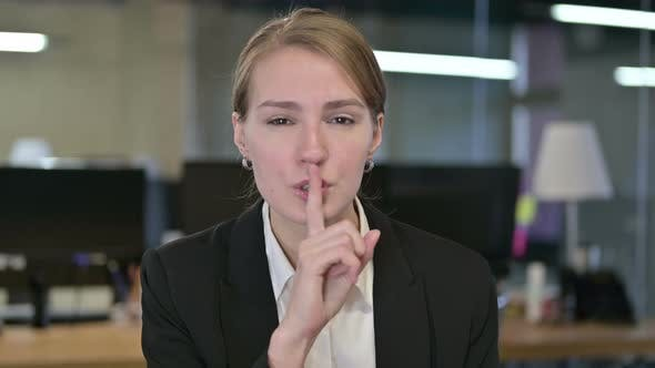 Thumbnail for Portrait of Young Businesswoman Putting Finger on Lips