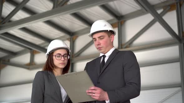 Young Man and Woman in Helmets with Documents at a Construction Site. Chiefs in Suits Discussing the