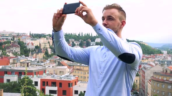 Thumbnail for Young Handsome Business Man Takes Photos Wirh Smartphone - City (Buildings) in Background