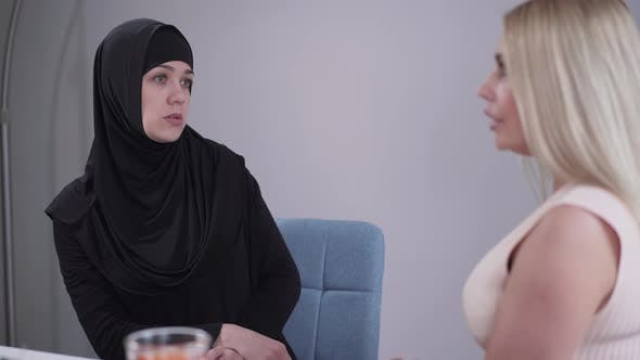 Cover Image for Portrait of Anxious Muslim Woman Talking with Unrecognizable Blond Caucasian Woman. Modest Eastern
