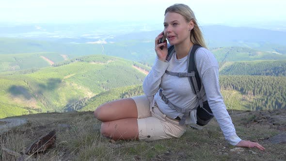 Thumbnail for A Young Beautiful Woman Sits on Grass on a Hilltop and Talks on a Smartphone