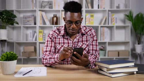 African man playing game online in smartphone