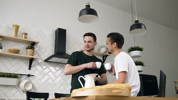 Thumbnail for Two Attractive Guys are Drinking Morning Coffee in Kitchen