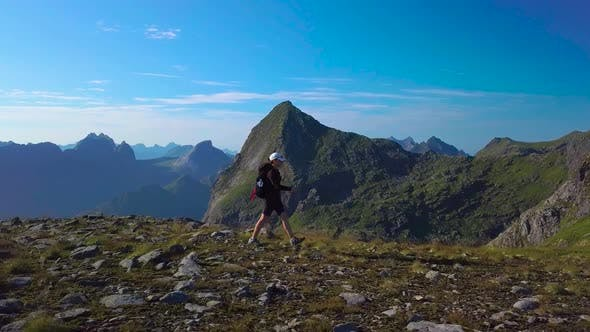 Thumbnail for Aerial View of Girl with a Backpack Goes on a Mountain Ridge