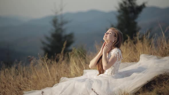 Thumbnail for Beautiful and Lovely Bride in Wedding Dress Sitting on Grass on Mountain Slope