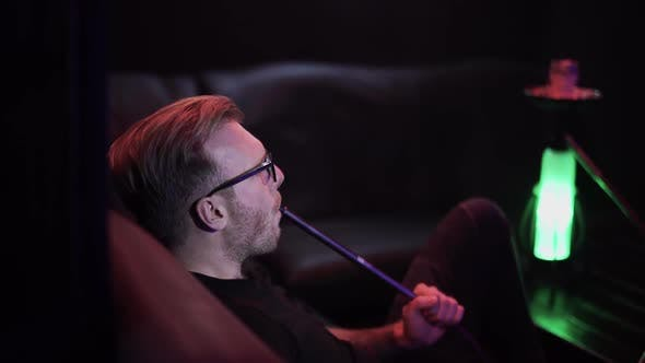 Thumbnail for Attractive Man in Glasses Exhales Steam in Night Club Sitting on Leather Couch