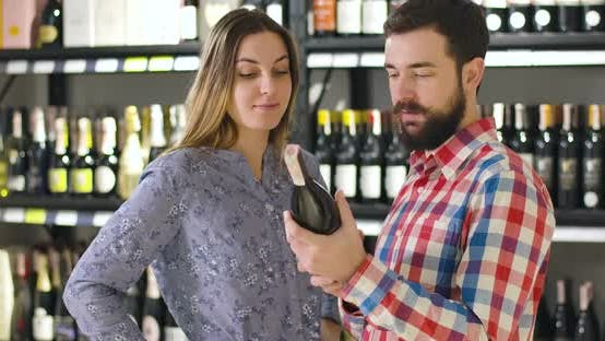 Thumbnail for Caucasian Man and Woman Discussing Red Wine As Standing at the Background of Shelves with Bottles in