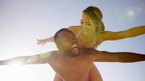 Thumbnail for Man giving piggyback ride to woman on the beach 4k