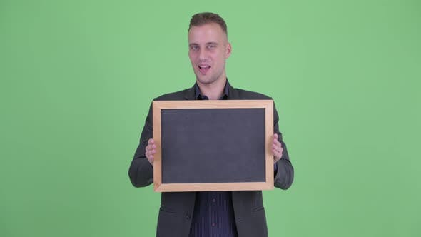 Thumbnail for Happy Handsome Businessman in Suit Holding Blackboard and Looking Surprised