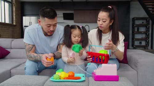 Happy Asian Parents Playing Cognitive Game with Baby Daughter
