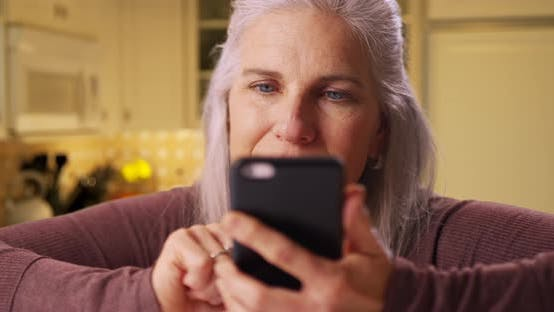Thumbnail for Mid aged white woman texting on a cellphone device