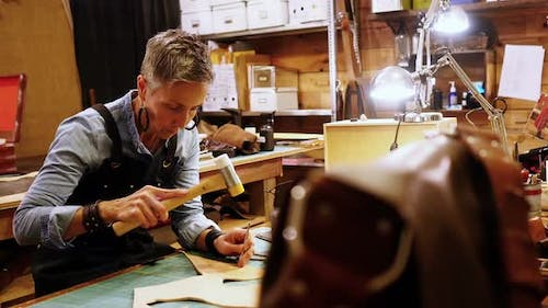 Attentive craftswoman nailing leather