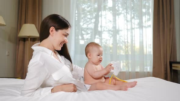 Thumbnail for Portrait of Attractive Young Woman with Her Adorable Child on Bed. Happy Maternity Concept. Loving