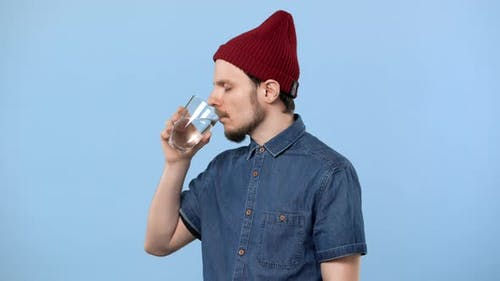 Portrait of Stylish Guy 20s with Beard and Curly Mustache Being Thirsty and Drinking Still Water