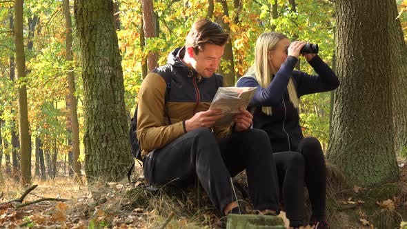 Thumbnail for A Hiking Couple Sits on the Ground in a Forest, He Reads a Map, She Looks Around with Binoculars
