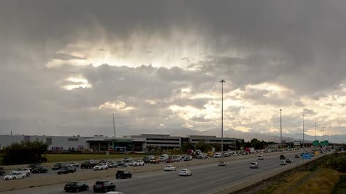 Time lapse of traffic moving on freeway as storm rolls overhead