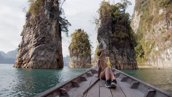 Woman in Boat with Tall Rocks and Cliffs in the Middle of the Lake in Thailand