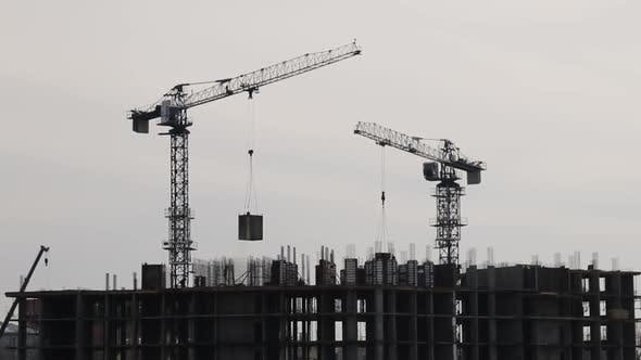 Silhouettes of Construction Cranes Working