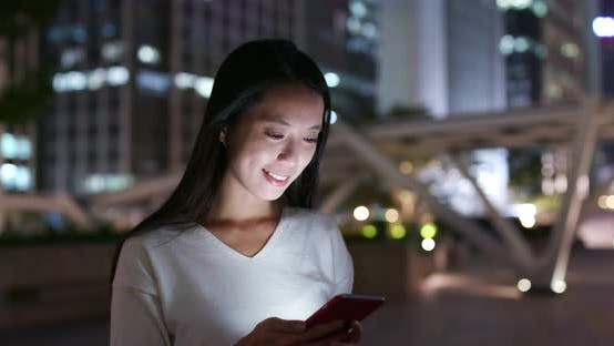Thumbnail for Woman look at the cellphone in city at night