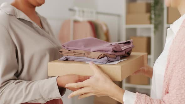 Thumbnail for Woman Handing Package and Clothes to Female Customer