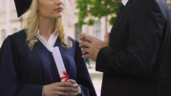 Thumbnail for Teacher gives life instructions to female graduate student in academic dress