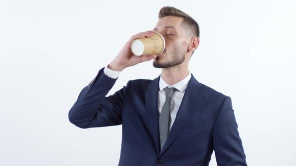 Thumbnail for Happy Businessman Drinking Coffee and Looking at Camera