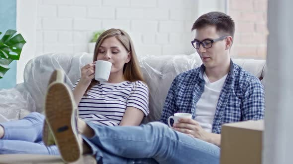 Thumbnail for Young Couple Drinking Coffee on Sofa